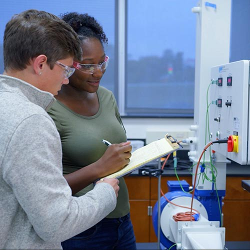 Two Cecil College students in the engineering lab working with equipment