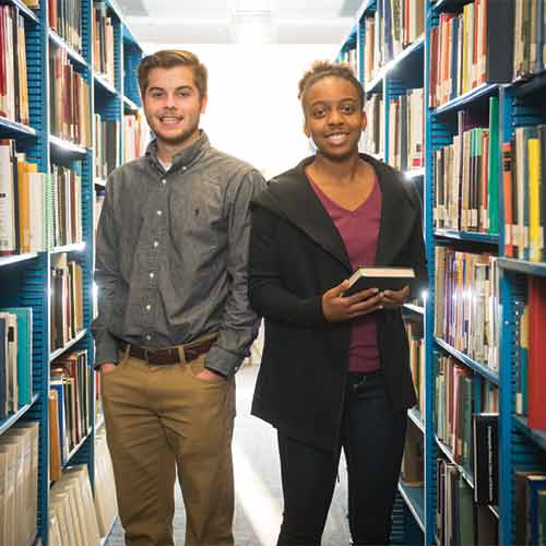 Two students standing in Cecil College library with books