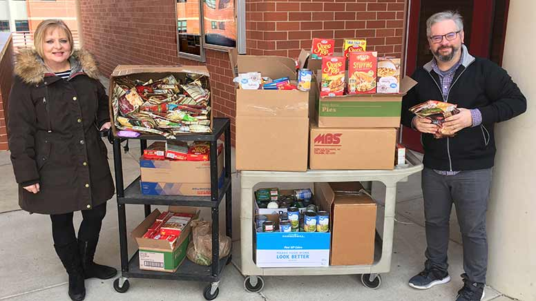 Shelly and Andrew from MST with a cart of food donations.