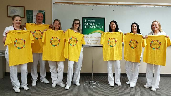 Nursing honor society students holding event t-shirts