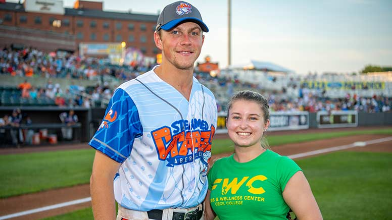Photo of Samantha Kohl standing next to an IronBirds baseball player.