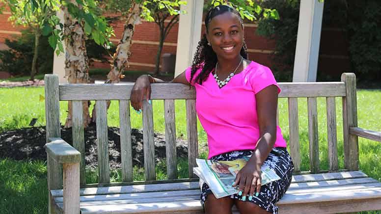 Sheena Butler sitting on bench in quad