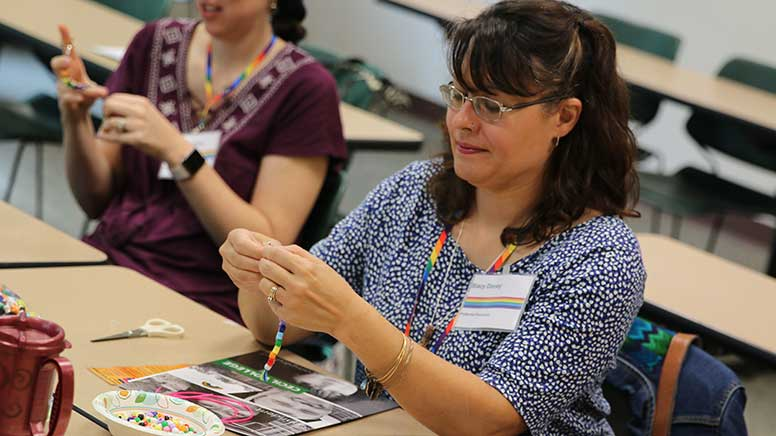 Woman making a rainbow bead bracelet
