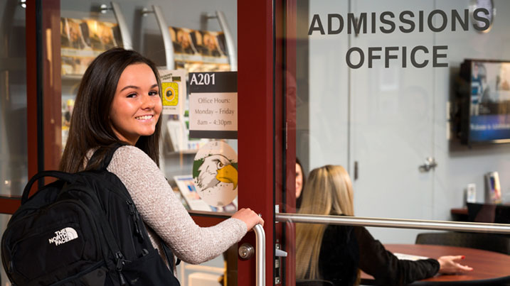 college student waking into Cecil College Admissions office