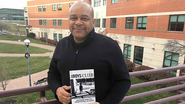 Dr. Beckles holding his latest book.