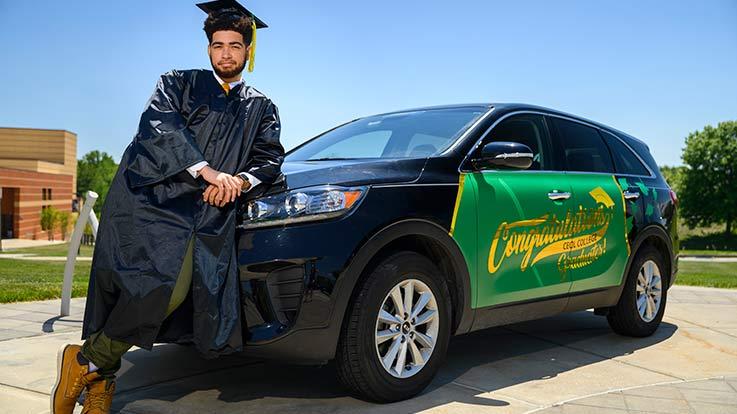 A graduate student leans against a car.