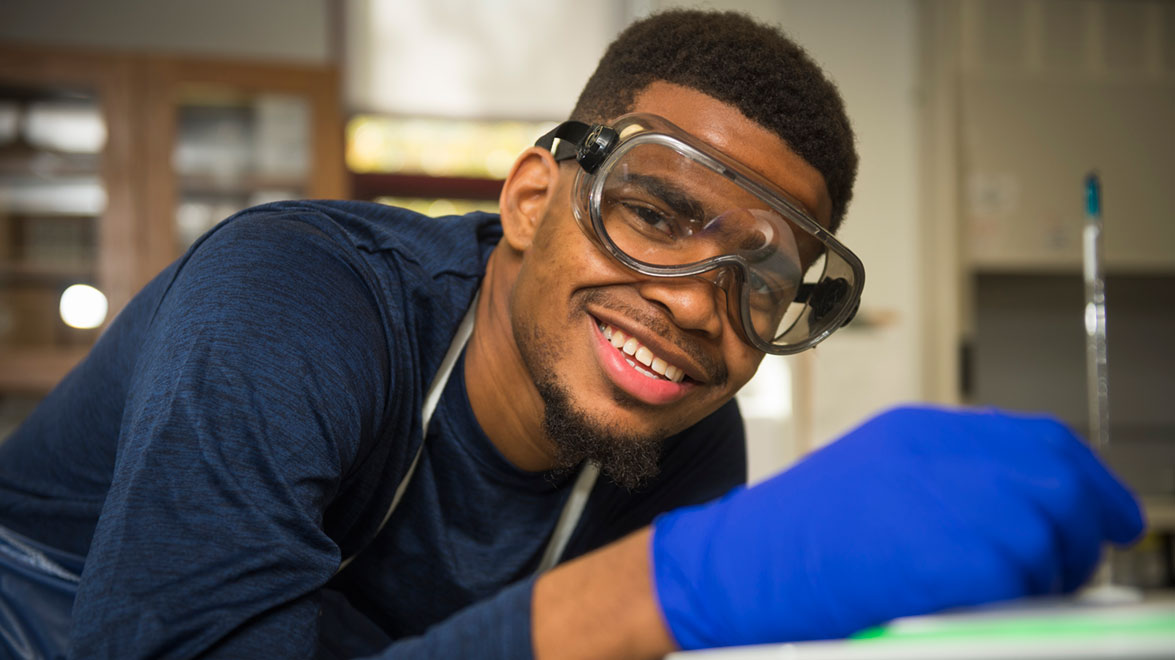 A student in a science lab with safety gear on.