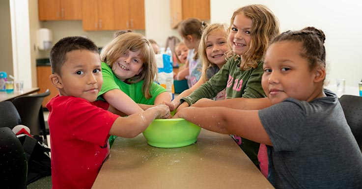 Kids with their hands in a bowl.