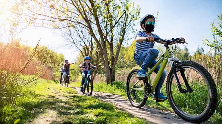 Kids riding bikes on a trail.