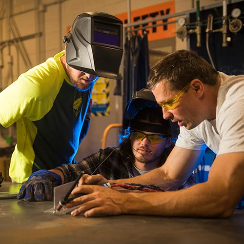 Two welding students with an instructor.